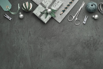 Christmas background with wrapped gifts, tags, cords and trinkets on dark textured background, copy-space