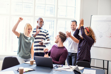 Smiling coworkers cheering together during an office meeting