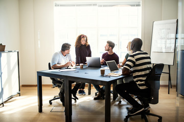 Diverse group of designers talking together around an office tab