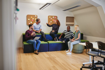 Designers talking together during a casual meeting in an office