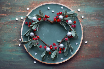 Red mistletoe Christmas wreath on round decorative tray on matching textured background