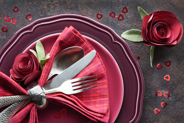 Flat lay with burgindy plates and crockery decorated with paper roses, Christmas or Valentine dinner setup