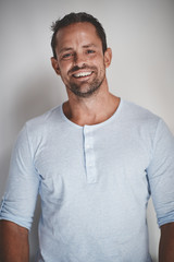 Male entrepreneur smiling while standing against a gray backgrou