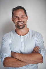 Entrepreneur smiling with his arms crossed on a gray background