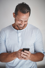 Laughing male entrepreneur standing against a gray background re