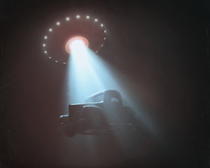Unidentified flying object lifting a car. Concept of alien abduction. Old style photo with noise of high ISO film. Effect of aging and wear due to time.