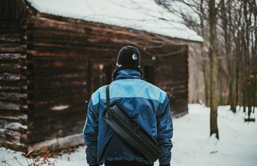 Photo of adventurer (hiker)  in snow covered forest in front of abandoned cottage (view from his back). Hiker Man in blue jacket standing in mountains with old destroyed cottage on background.