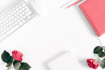 Female desktop, сomputer keyboard, notebook, bouquet roses on white background. Flat lay, top view, copy space