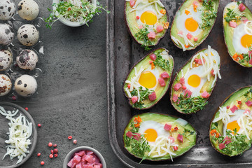 Keto diet dish: Avocado boats with ham cubes, quail eggs, cheese and pepper on dark