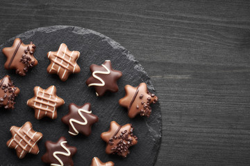 Star-shaped chocolates on dark textured background, copy-space
