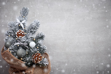 Small Christmas tree in sackcloth decorated with red baubles and berries on light stone with copy-space