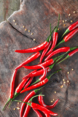 Close-up on red hot chili peppers on rustic wood, flat lay