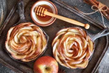 Homemade puff pastry with rose shaped apple slices baked in iron skillet