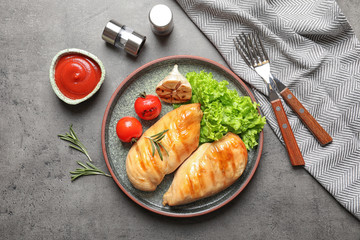 Fried chicken breasts served with sauce and garnish on grey table, top view
