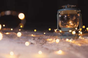 Lantern with burning candle and Christmas lights on white snow outdoors. Space for text