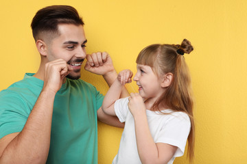 Little girl and her father flossing teeth on color background