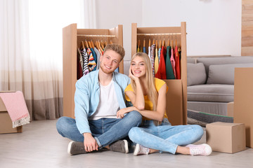 Happy young couple sitting near wardrobe boxes indoors