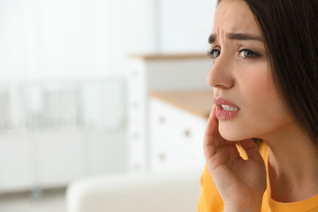 Young woman suffering from strong tooth pain at home, space for text