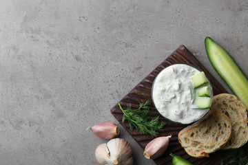 Tzatziki cucumber sauce with garlic, dill and bread on grey background, top view. Space for text