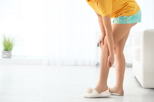 Young woman suffering from leg pain at home, closeup. Space for text