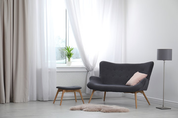 Comfortable sofa near window with open curtains in elegant room interior