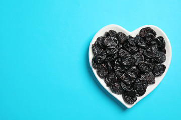 Heart shaped plate of sweet dried plums on color background, top view with space for text. Healthy fruit