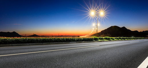City road and bright street lights landscape at sunset,panoramic view
