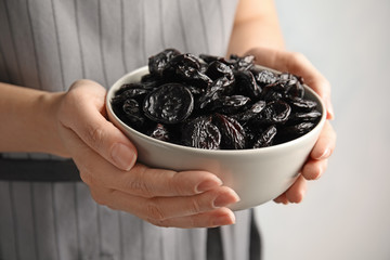 Woman holding bowl of dried plums, closeup. Healthy fruit