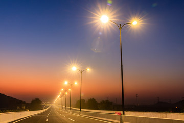 Spoed Foto op Canvas Nacht snelweg City road and bright street lights landscape at sunset