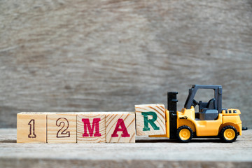 Toy forklift hold block R to complete word 12mar on wood background (Concept for calendar date 12 in month March)