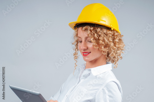 7f36ed53e23 Business woman engineer in yellow safety helmet is looking to tablet ...
