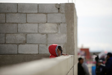 A child plays near a house where five members of a family were found dead, according to local media, in Ciudad Juarez