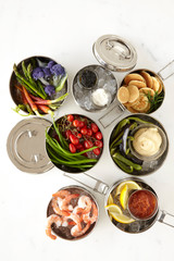 Silver tiffins filled with appetizers and crudite