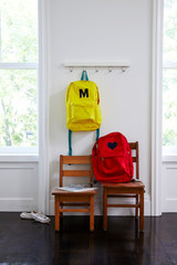 Child's backpacks in room with 2 chairs