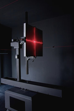 Red laser beams light effect on led luminaire on stand photometric lab
