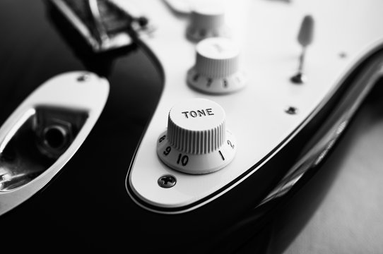 Close-up of electric guitar, in black and white.