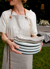 Woman in apron bringing plates and linens to table outdoors