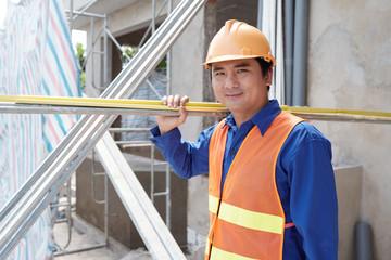 Fototapeta Portrait of smiling Vietnamese worker carrying construction materials obraz