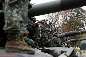 Soldiers sit on an M60A3 tank for a group photograph after an anti-invasion drill to test readiness ahead of Lunar New Year, in Taichung