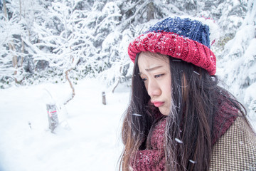 Portrait of woman feeling unhappy and very cold under snowy weather and hair was frozen by snow.