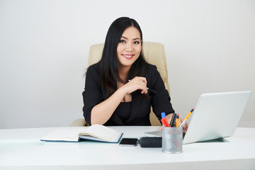 Beautiful smiling Vietnamese businesswoman working on project at her desk in office