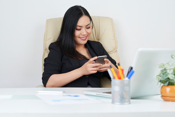 Attractive smiling businessman using messenger on smartphone for communication with colleagues