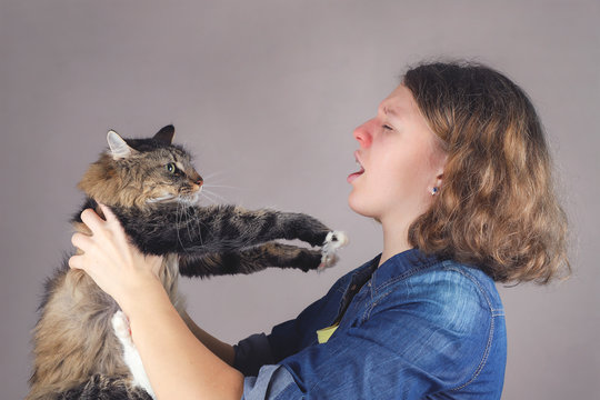 A teenaged allergic girl holds a maine coon cat.