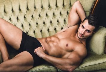 Portrait of handsome young man with stylish haircut in black underwear posing on the couch. Perfect body & skin.
