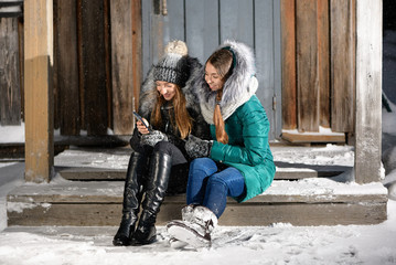 Two happy сaucasian girls are sitting on the porch of a village house in winter. The smiling young womens with mobile phone are on their farm.