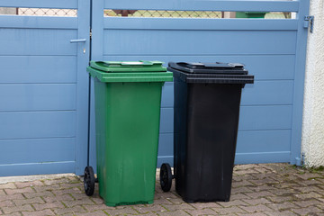 Two large outdoor grey and green garbage bin in home garden