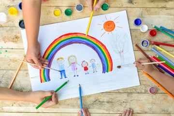 Happy family concept. Co-creation. Children hands draw on a sheet of paper: father, mother, boy and girl hold hands against background of rainbow and sunny sky. Close-up.