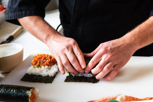 Chef making sushi rolls in the bar