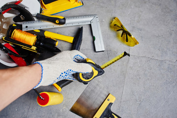 The concept of repair. Male hand holding a tape measure against a background of construction tools. First person view.