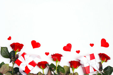 Border of gifts, rose flowers and decorative hearts on white background. Place for text, top down composition.